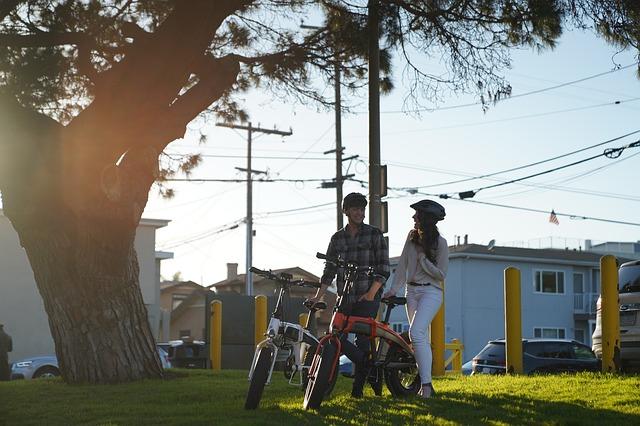 Chlapec s dívkou stojící ve městě u svých elektrokol