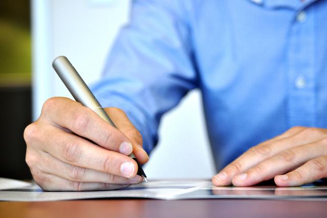 Muž v modré košili podepisuje listinu stříbrným perem
