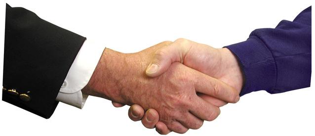 Potřesení rukou muže v obleku a muže v mikině